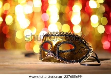 Beautiful carnival mask on table on bright background