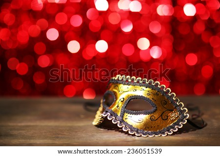 Beautiful carnival mask on table on red background - stock photo