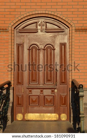 Beautiful carved wooden mahogany door with surround relief and decorative cross located in the brick wall of the Christian Church - stock photo