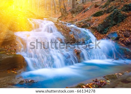 beautiful cascade on a mountain river by a sunny day - stock photo