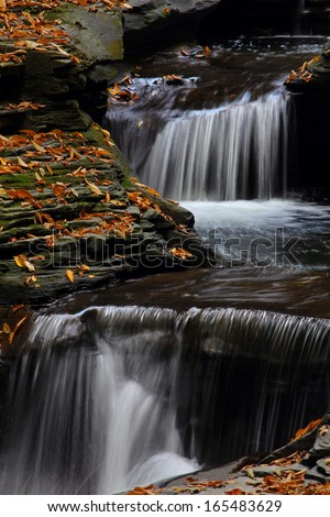 Beautiful cascading falls with Autumn Leaves and rock formations. - stock photo