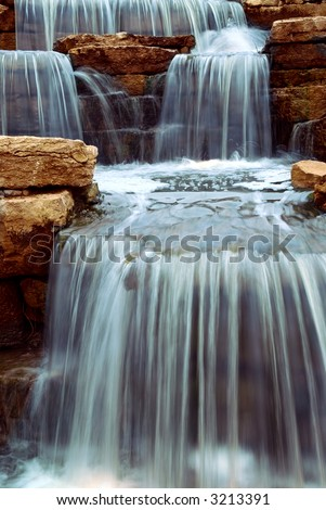 Beautiful cascading waterfall over natural rocks, landscaping element - stock photo