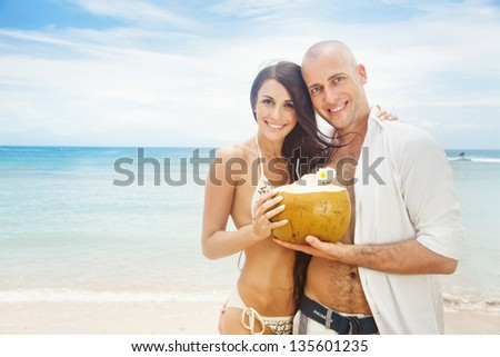 beautiful casual couple with coconut cocktail - stock photo
