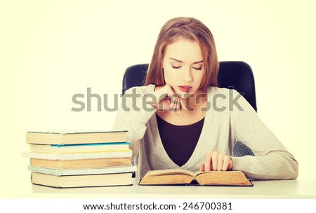 Beautiful casual student woman sitting by stack of books. - stock photo