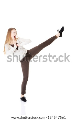 Beautiful casual woman doing a kick. Isolated on white.