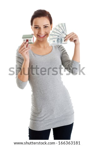 Beautiful casual woman holding money and house. Isolated on white.