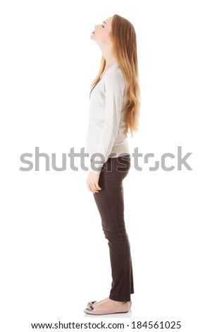 Beautiful casual woman is looking up. Side view. Isolated on white. - stock photo
