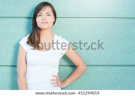 Beautiful casual woman posing with hand on waist being serious outside on green wall with copy text space - stock photo
