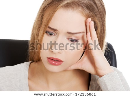 Beautiful casual woman student worried, scared is sitting by a desk and stack of books. Isolated on white. - stock photo