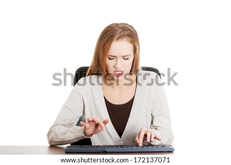 Beautiful casual woman writing on keyboard with anger.Isolated on white. - stock photo