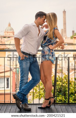 Beautiful casual young couple portrait outdoors in hotel terrace.