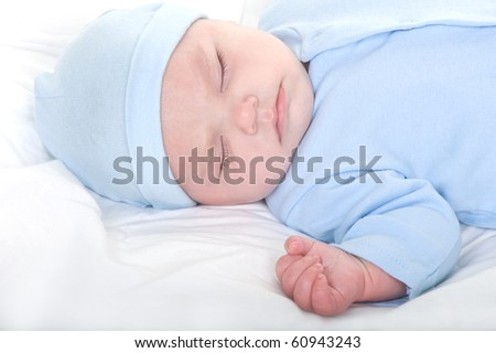 Beautiful Caucasian baby boy sleeping in blue pajamas and hat - stock photo