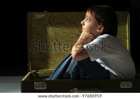 Beautiful Caucasian bliss boy sitting in the suitcase on white background