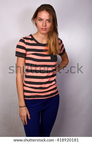 beautiful Caucasian blond girl student posing in studio isolated on white background, striped polo. hand on waist - stock photo