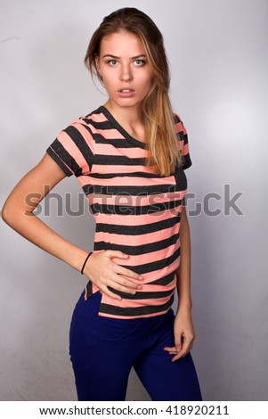 beautiful Caucasian blond girl student posing in studio isolated on white background, striped polo. hand on waist. sexy - stock photo