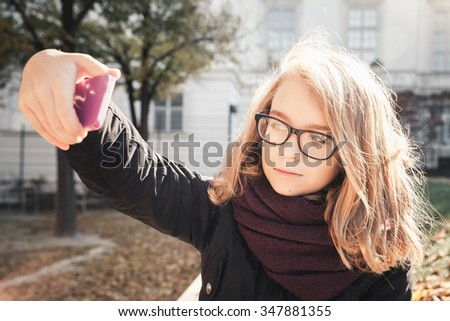Beautiful Caucasian blond teenage girl taking photo on her smartphone in autumnal park, vintage style tonal correction photo filter - stock photo