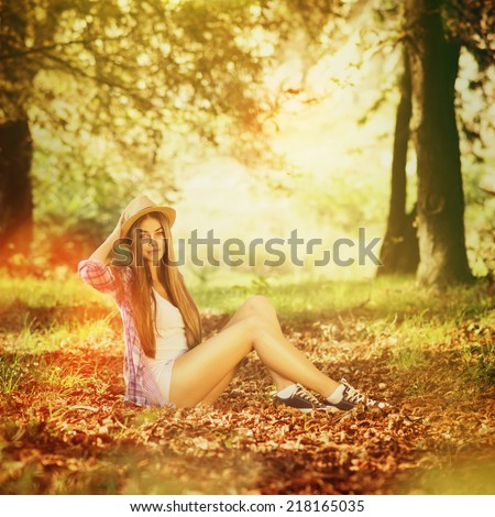 Beautiful Caucasian blonde long haired teenage girl with hat sitting in nature in autumn among the leaves looking at camera smiling. Square format, warm colors. - stock photo