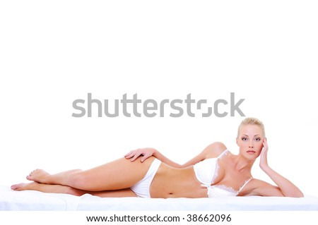 Beautiful caucasian blonde woman with perfect sexy body lying down on the bed