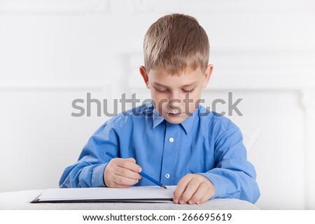 beautiful, caucasian boy draws a pencil on the album - stock photo