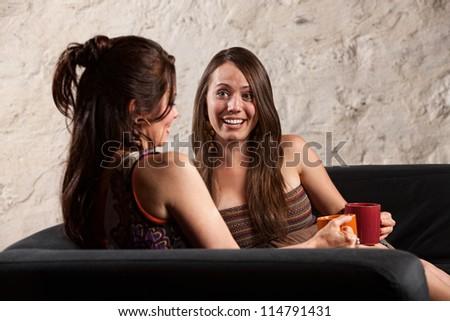 Beautiful Caucasian brunette ladies sitting indoors talking - stock photo