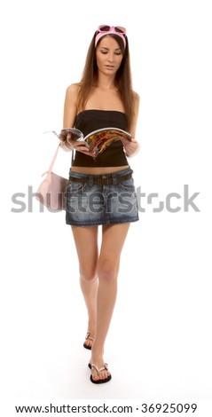 beautiful caucasian brunette model in jeans skirt walks and reads magazine - stock photo