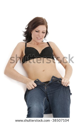 beautiful caucasian brunette struggling to get into her too tight blue denim jeans