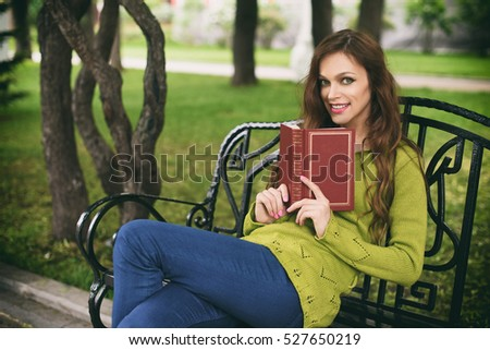 Beautiful caucasian brunette young woman at park. Girl in green sweater, a book in her hands, reading on a bench, smiling.