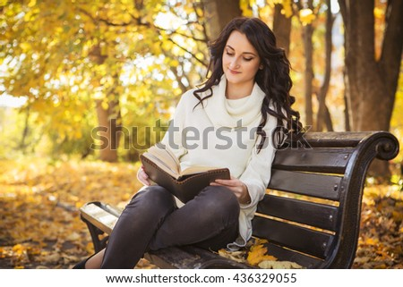 Beautiful caucasian brunette young woman in warm autumn day at park. Yellow leaves and sunshine. Fall season. Woman in white sweater, a book in her hands,reading sitting on a bench,smiling. Copy space - stock photo