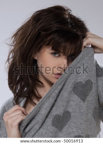 beautiful caucasian brunette young woman wearing a sweater with hearts on it - stock photo