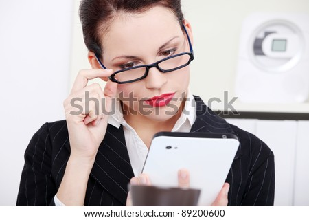 Beautiful caucasian businesswoman in glasses looking at the tablet in the office. - stock photo