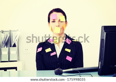 Beautiful caucasian businesswoman sitting in the office with post it notes on her body. - stock photo