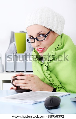 Beautiful caucasian businesswoman wrapped on green blanket feeling cold. - stock photo