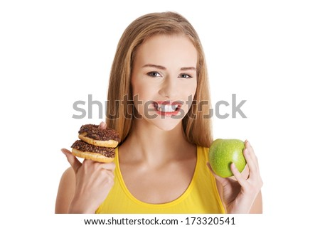 Beautiful caucasian casual woman with doughnuts and apple. Isolated on white.