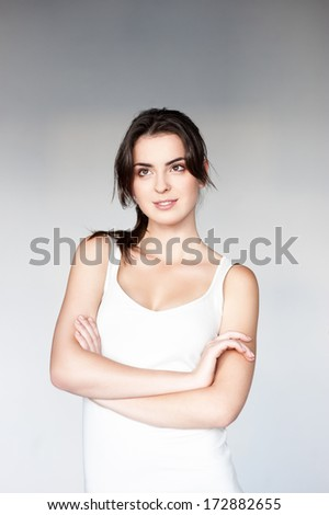 beautiful caucasian cheerful young woman  in white singlet holding red apple over gray background - stock photo