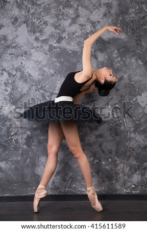 Beautiful caucasian contemporary ballet-dancer in black scene dress with dark hear posing on grey studio background