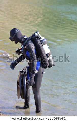 Beautiful caucasian diver woman is preparing to enter the water. Exploring the depths