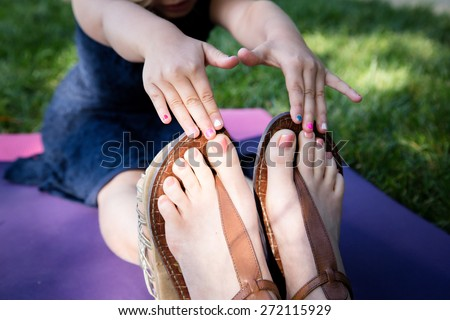 Beautiful Caucasian ethnicity mother and daughter stretching and touching each other  toes at park - stock photo