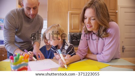 Beautiful caucasian family drawing for her young child.