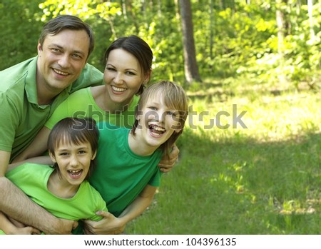 Beautiful Caucasian family of four in green shirts - stock photo
