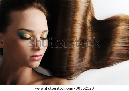Beautiful caucasian female face with long luxuriant hair - closed eyes - stock photo
