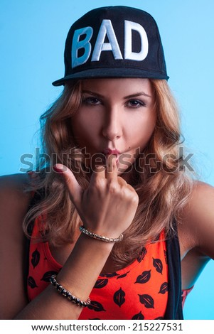 Beautiful caucasian female in black hat looking at camera in studio - stock photo