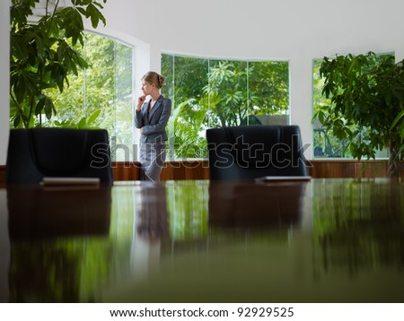 Beautiful caucasian female manager looking out of the window in office. Side view, copy space - stock photo