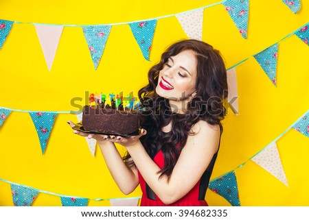 Beautiful caucasian girl blowing candles on her cake. Celebration and party. Having fun. Young pretty woman in red dress and birthday hat is laughing. - stock photo