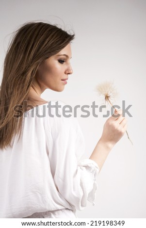 Beautiful caucasian girl holding a dandelion, wearing a white blouse with light grey background