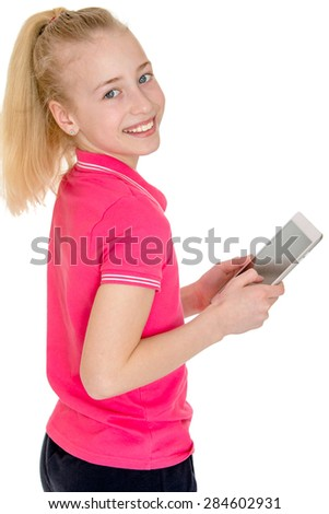 Beautiful Caucasian girl holding a tablet and smiling while standing sideways to the camera- isolated on white background - stock photo