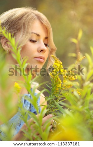 Beautiful caucasian girl in a blue dress smelling yellow wildflowers - stock photo