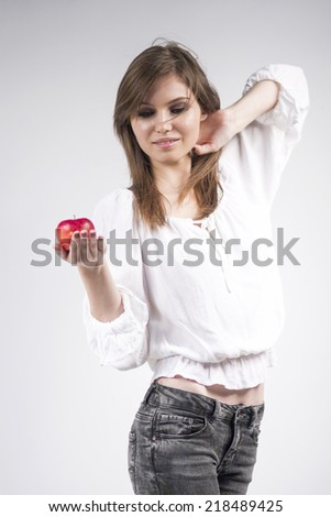 Beautiful caucasian girl wearing a white blouse, holding a red apple with light grey background  - stock photo