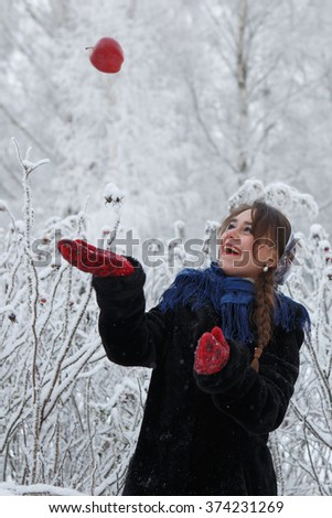 Beautiful caucasian girl with chestnut hair plays with red apple among branches covered with frost - stock photo