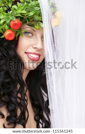 Beautiful caucasian girl with perfect smile half hidden behind white veil, in summer gown and flowers in hair. - stock photo