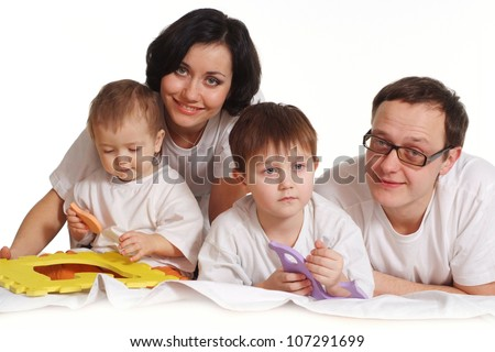 Beautiful Caucasian happy family of four on the bed